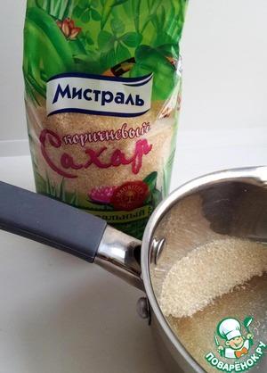В сотейник насыпать 130 гр коричневого сахара и влить 2 ст. л. воды (только чтобы немного смочила сахар). Поставить сотейник на средний огонь и, помешивая, довести до кипения. После закипания дать карамели покипеть 3-5 мин., не мешая.