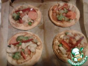 Выложить на подрумянившиеся пиццы промаринованные овощи с арахисом и отправить в духовку еще на несколько минут.