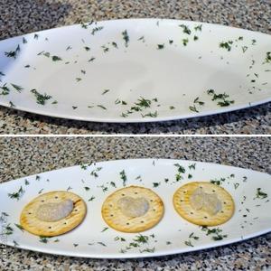 Теперь можно собирать закуску. Беру тарелку, на которой буду подавать, и присыпаю её укропом, можно положить орешки. На крекеры кладу немного грибного соуса.
