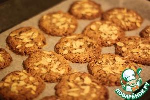 Посыпьте печенье миндальной стружкой и отправьте на 30 минут в предварительно разогретую до 180 градусов духовку.