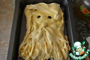 """8. Переносим наш """"реквизит"""" на пирог. Над бородой кладём шарик - это нос. """"Щёчки"""" проткнули вилкой, чтобы Дед Мороз не раздулся. Глазки сделали из маслин. Смазали взбитым яйцом."""