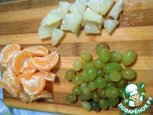 Фрукты помыть и очистить (какие надо). Мандарины разделить на дольки, виноград разобрать на отдельные ягоды, а кольцо ананаса порезать кусочками.