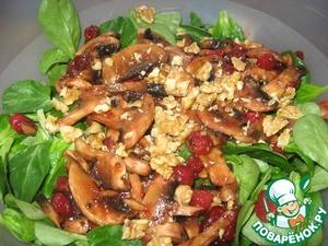 Выкладываем на салат шампиньоны с клюквой и посыпаем рублеными грецкими орехами.