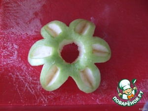 Now cut along the contour of the petals of the extra flesh of the Apple to make like a flower. Then in the middle to cut the hole.
