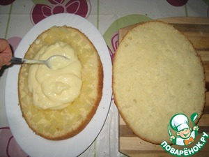 Cakes impregnated with syrup from pineapple (if put on cakes immediately after baking, do not overdo it, and you will become very viscous, the biscuit is better to stand for several hours); 3-4 rings of pineapple chopped and spread on the bottom cake, sprinkle half of the cream and flatten.