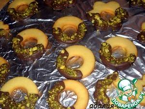 На водяной бане растопить около 100 г шоколада. Каждое печенье окунуть в шоколад и посыпать орешками.