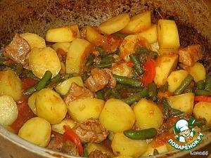 Небольшие кусочки мяса обжарить в казане на растительном масле (жире).    Добавить нашинкованный лук. Далее нарезанную кольцами морковь и чеснок. Хорошо прожарить, добавить немного воды и томатную пасту. Тушить под крышкой до готовности мяса. Затем добавить зеленой стручковой фасоли, молодой картофель, молотой зиры и Вегету. Влить немного кипятка, чтобы содержимое в казане не подгорело.