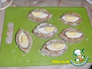 Отварить яйца, разделать на четвертинки. Из фарша слепить лодочки, обвалять чуть в муке, разложить вовнутрь яйца - дольки.