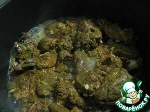 3. Духовку разогреть до 150 градусов. Чеснок мелко нарезать и обжарить его в большой чугунной кастрюле, затем положить в нее семена горчицы.    Следом добавить мясо вместе с маринадом. Слегка посолить, довести до кипения и закрыть крышкой. Отправить кастрюлю в духовку на 1 час.