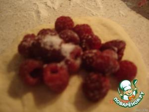 Тесто разделить на небольшие шарики, примять рукой и уложить малинку, присыпать немного сахаром.