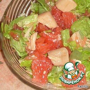 Листья салата вымыть и обсушить.    Грейпфрут очистить, вынуть мякоть и разломить на небольшие кусочки, 2-3 дольки отложить.   Приготовить заправку:   смешать сок 2 долек грейпфрута, оливковое масло, измельченный зубчик чеснока. Посолить, поперчить по вкусу.    Положить в салатник в произвольном порядке салатные листья, гребешки и нарезанную мякоть. Полить заправкой.