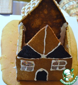 Fill seams with icing and glue the tube to the small end. After complete drying apply a roof. Protein prepared from the latest latest batch of frosting and decorate the house, fill with glaze exposed seams design, sprinkle with topping, spread the marmalade the fence and set up the Christmas tree, attached to the glaze.