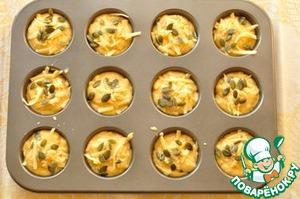 Разлейте тесто по подготовленным формочкам. Посыпьте оставшимся сыром и тыквенными семечками.    Выпекайте минут 20 до золотисто-коричневой корочки. Готовые маффины оставьте в формах на 10 минут, а затем выньте. Можно подавать теплыми.