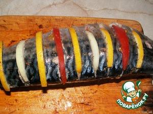 Рыбу натереть солью, перцем, приправой.    С двух сторон сделать глубокие надрезы. В каждый надрез положить по лимону, помидору и луку (чередовать).