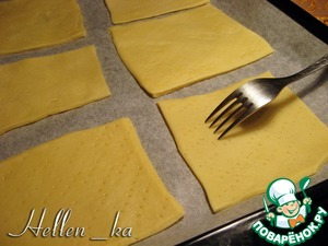 Coat the baking pan with parchment. Preheat the oven to 180 degrees.  Take out the dough. Table sprinkle with flour and roll out thin layer (2 mm), cut out cookies (I did squares) and place on a baking sheet. Pinned the dough with a fork.