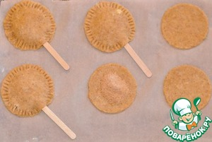 Lay half the circles on a baking tray lined with baking paper. Each put a spoonful of sugar toppings and put a wooden stick if you use. Cover with the remaining circles, tightly Zadajte edges and apply a fork pattern around the perimeter.