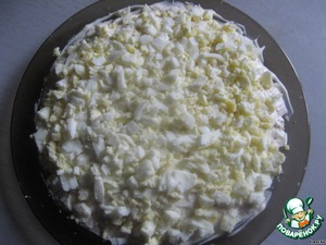 Яйца измельчаем, выкладываем на тарелку 4-ым слоем и смазываем майонезом.