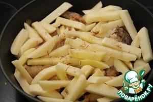 Добавить картофель в сковороду к цыпленку, еще разок посолить, посыпать шафраном и тушить под крышкой на медленном огне 20 минут. Перемешать один раз, через пять минут после того, как заложили картофель.