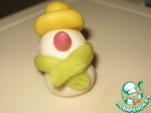 From colored in light green the color of the marzipan roll out the long block. With the edges of the block press using pressure and make several cuts. Secure the scarf around the neck of the snowman. From the little pink ball make a carrot for the nose. Make a well in the head recesses for the eye with a sharp stick.