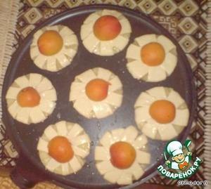 """1. тесто размораживаем при комнатной температуре, раскатываем скалкой и режем на полоски шириной 2-3 см.    2. ананасы извлекаем из сиропа и просушиваем салфеткой.    3. каждое колечко ананаса обматываем ленточкой из теста,    смазываем взбитым желтком.    Серединку закрываем половинкой абрикоса, укладываем """"ромашки"""" на противень, смоченный водой,    отправляем в таком виде на противне в духовку"""