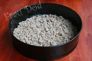Застелить листом пергамента разъемную форму для торта. Сверху выложить хлебную массу, уплотнить. Поставить на 15 мин в холодильник.