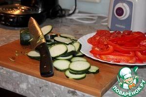 Все овощи вымыть. Из перца удалить сердцевину, мякоть нарезать тонкими полосками. Помидоры и цуккини нарезать кружками толщиной примерно 0.5 см.