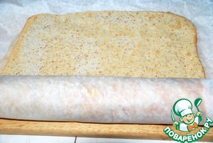 Get almond sponge cake, carefully remove the paper and wrap the roll along with the paper.