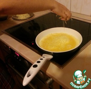 Next in the pan, where the heated oil, pour half of egg mixture. Increase the heat to medium. As soon as the omelet begins to sinter at the edges, about 3-5 minutes, sprinkle 1/4 of the grated cheese.