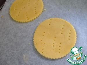 Вырезать печенье, наколоть вилкой.    Убрать в холодильник, как минимум на 1 час.   Также можно поместить песочную основу в форму для маффинов, чтобы они не деформировались во время выпекания.   Разогрейте духовку до 200*С.   Выпекать 12-15 минут.   Дать печенькам полностью остыть.