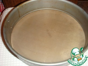 The bottom of a split baking dish with a diameter of 26 cm covered with baking paper.
