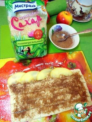 Тесто слегка раскатать (необязательно), посыпать смесью сахара и корицы, нарезать полосками примерно 1,5 - 2 см. Выложить внахлёст дольки яблок.