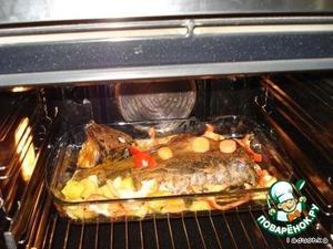 """Разогреваем духовку до температуры 180 градусов в режиме """"гриль"""" и помещаем в нее форму или противень с рыбой и овощами.    Запекать минут 30-40 до золотистой корочки сначала с одной стороны, потом перевернуть и так же запечь другую сторону."""