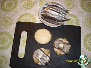 Кружочки батона намазать горчичным маслом.    Кильку разобрать на филе и уложить на хлеб.    Украсить огурчиком маринованным и кружочками лука. Сверху выдавить по маленькой капельке майонеза.
