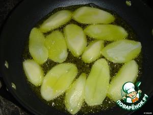 Очистить картофель, нарезать вдоль и обжарить до полуготовности с двух сторон.