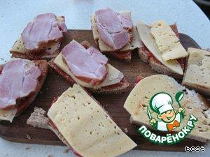 Хлебные ломти смазать хорошенько кетчупом. На каждый ломтик положить сыр и на половину ломтиков положить ветчину. Сформировать сэндвичи.