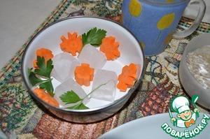 В мисочку выложим нарезанную фигурно морковь и зелень, самый толстый и ровный кусочек моркови положим на дно, на нем будет стоять верхняя форма во время заморозки.