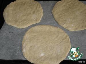 Когда тесто подойдет его обмять и разделить на 3 равные части, раскатать лепешки,наколоть их немного вилкой,переложить на противень застеленный промасленной бумагой.