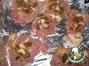Выложить мясо. На каждый кусочек положить грибы и немного измельчённого чеснока.