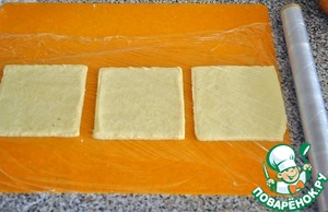 Roll the dough and cut into squares. Can choose the form you prefer. If you do not as a portion dish, and a big cake, then attach the form to the test and find the very this form where you will later bake. Close the top cling film and invert onto the Board.