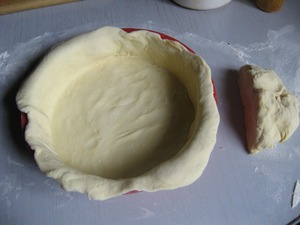 Divide the dough into two pieces, approximately 1/4 to defer - it will be cap, and the remaining roll the dough (not too thinly, because it turns out a lot of toppings and the bottom can be torn) and put in the form