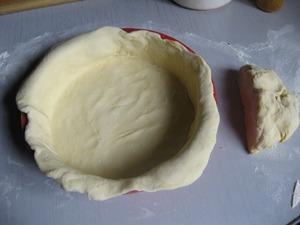 Тесто разделить на две части, примерно 1/4 отложить - это будет крышечка, а оставшееся тесто раскатать (не очень тонко, т. к. начинки получается много и дно может порваться) и уложить в форму