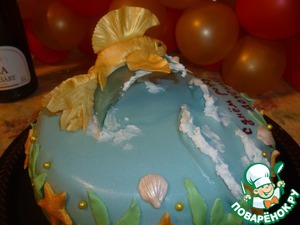 Finished cake by the construction of a fish on a wave.