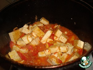 Next, put the sliced Tofu in a large kettle, fry for a further 2 minutes and sprinkle greens with crushed garlic and cover the cauldron. Stew for 5 minutes on low heat. Spread on a plate and pour soy sauce.