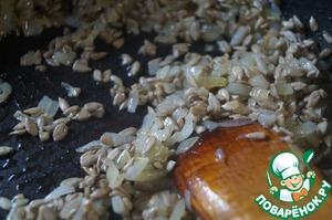 Добавить к луку семечки и продолжить обжаривание в течение 2-3 минут, помешивая.