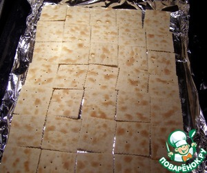 The oven heated to 180 degrees, baking tray lay with foil and on it spread a crackers. Instead of crackers you can use dry bread, thinly sliced.