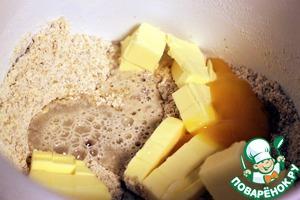 Холодное сливочное масло нарезать кусочками и добавить к тесту.   Добавить желток и 2 столовые ложки холодной воды.