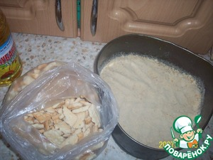 Смазываем форму маслом и трем на терке печенье (я покупаю лом, он дешевле), высыпаем в форму и ровняем, толщина слоя - примерно 0,5 - 0,7 см.