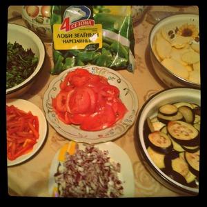 Нарезать баклажаны, картофель, помидоры - кружочками, перец - соломкой, зелень и лук - мелко.