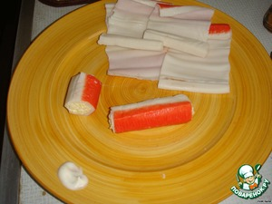 Cheese salad( cheese, egg) to squeeze out 2 teeth. garlic and mayonnaise. On the edge, deployed crab sticks put 2-3 tbsp cheese salad and wrapped in a roll, while the edge of the sticks lubricated with a drop of mayonnaise to the roll is not unfolded, and cut in half.