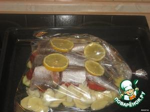 Помидор порезать кружочками.   В пакет для запекания уложить слоями:   картофель, кабачок, помидор, рыба, лимон, по краям уложить цветную капусту.   Каждый слой немного посолить.
